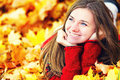 Young woman lying down in autumn leaves smiling Stock Images