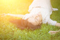 Young woman lying on the grass cute in sunshine soft focus with shallow depth of field Stock Photo