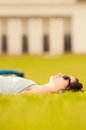 Young woman lying on green grass with earphones Royalty Free Stock Photo