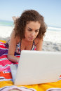 Young woman lying on her beach towel while using a laptop Royalty Free Stock Photo