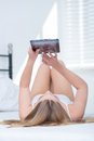 Young woman lying on her bed using a tablet pc back holding it up in the air above as she surfs the internet Royalty Free Stock Photos