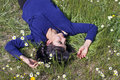 Young woman lying in a meadow among daisies Royalty Free Stock Photo