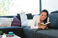 Young woman lying reading book couch sofa Stock Photos