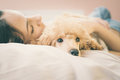 Young woman is lying and sleeping with poodle dog in bed. Royalty Free Stock Photo