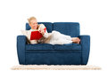 Young woman lying on a sofa reading a book Stock Image