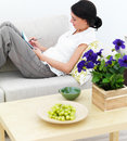 Young woman lying on sofa writing in notepad Royalty Free Stock Photo