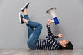 Young woman lying and speaking in megaphone Royalty Free Stock Photo