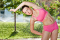 Young woman makes side bends outdoors Royalty Free Stock Photo