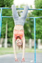 Young woman making antigravity yoga exercises. Woman doing lifting up on the gym bar. young fitness girl pulls up on street Royalty Free Stock Photo