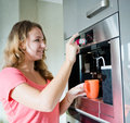 Young woman making coffee cup machine kitchen interior happy Royalty Free Stock Photos