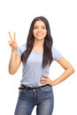 Young woman making a peace sign vertical shot of cheerful with her hand and looking at the camera isolated on white background Royalty Free Stock Images