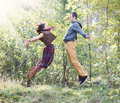 Young woman and man in bright clothes jumping to meet each other women men the park Royalty Free Stock Photo