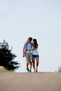 Young woman and man is walking on a road in summer outdoor Royalty Free Stock Image