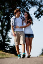 Young woman and man is walking on a road in summer outdoor Stock Images