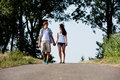 Young woman and man is walking on a road in summer outdoor Royalty Free Stock Photography