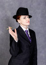 Young woman in manly style with mini cigar on gray background, girl in man`s suit and tie, white shirt and hat Royalty Free Stock Photo