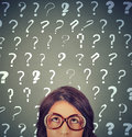 Young woman with many question marks above her head Royalty Free Stock Photo