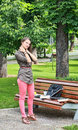 Young woman massaging her nape in a park near bench during short break of work on laptop Royalty Free Stock Photos