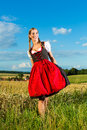 Young woman on meadow wearing dirndl bavarian and smiling Stock Photography
