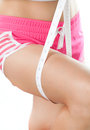 Young woman measuring her thigh with measuring tape Royalty Free Stock Photo