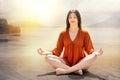 Young Woman Meditating At Rive...