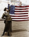Young woman in military uniform holding up an American flag Royalty Free Stock Photo
