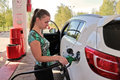 Young woman motorist fills her car with benzine at gas station beautiful look filling gun Stock Photos