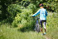 Young woman with mountain bike outdoors Stock Photo