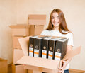 Young woman moving house to new home holding cardboard boxes Royalty Free Stock Photo