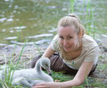 The young woman near a baby bird of a swan on the bank of the lake Royalty Free Stock Images