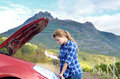 Young woman near broken car needs assistance looking under opened hood Stock Photography