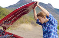Young woman near broken car needs assistance looking under opened hood Stock Images