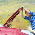 Young woman near broken car needs assistance looking under opened hood Royalty Free Stock Photos