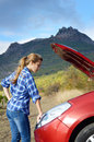 Young woman near broken car needs assistance looking under opened hood Stock Image