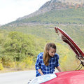 Young woman near broken car needs assistance looking under opened hood Royalty Free Stock Image