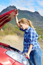 Young woman near broken car needs assistance looking under opened hood Stock Photos