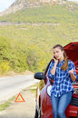 Young woman near broken car speaking by phone needs assistance Royalty Free Stock Image