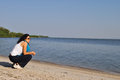Young woman near the water crouched on shore of lake victoria Stock Images