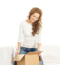 A young woman opening a cardboard box Stock Images