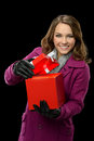Young woman opening gift box isolated over black background Royalty Free Stock Images