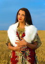 Young woman with ornamental dress and white fur standing on a wheat field with sunset natural background Royalty Free Stock Images