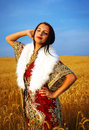 Young woman with ornamental dress and white fur standing on a wheat field with sunset natural background Royalty Free Stock Photo