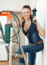 Young woman in overalls with drill portrait of the interior Stock Photography