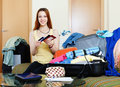 Young woman packing documents into suitcases going on holiday Stock Images