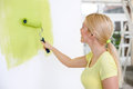 Young woman painting wall in green Royalty Free Stock Photo