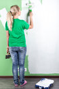 Young woman paints the wall full length portrait Royalty Free Stock Images