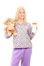 Young woman in pajamas holding teddy bear and baby bottle a isolated on white background Royalty Free Stock Photos