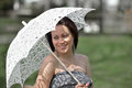 Young woman with parasol beautiful hispanic in strapless grey dress holding a white lace over her shoulder in garden smiling and Royalty Free Stock Photography