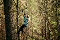 Young woman in park clambering with ropes in forest. Royalty Free Stock Photo