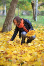 Young woman in the park gathering autumnal leaves beautiful orange scarf fallen Stock Photography